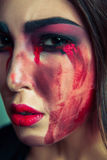 Portrait of freak monster with mess dirty colored makeup on her face. crying woman with red bloody tears and hand. halloween conce Royalty Free Stock Image