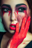 Portrait of freak monster with mess dirty colored makeup on her face. crying woman with red bloody tears and hand. halloween conce Royalty Free Stock Images
