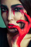Portrait of freak monster with mess dirty colored makeup on her face. crying woman with red bloody tears and hand. halloween conce Royalty Free Stock Photo