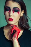 Portrait of freak monster with mess dirty colored makeup on her face. crying woman with red bloody tears and hand. halloween conce Stock Images