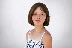 Portrait of freckled little girl with dark short hair, hazel eyes and thin lips wearing black and white dress, posing at camera ag Stock Photography