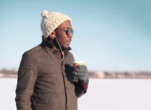 Portrait free young african man enjoying drinking coffee over blue sky in cold winter looking profile Stock Photo