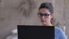 Portrait of freelancer girl in glasses working on laptop online sitting at home close-up