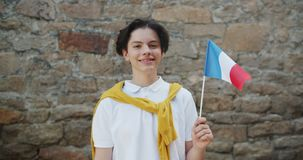 Portrait of French teenager holding national flag of France smiling outdoors. Portrait of joyful French teenager holding national flag of France smiling outdoors stock footage