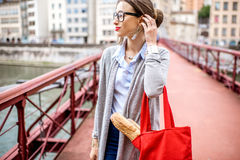 Portrait of a french woman. French woman walking with baguette on the bridge in Lyon city Stock Photos