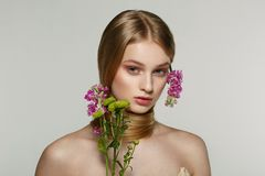 Portrait of fresh and beautiful blonde girl with pink flowers royalty free stock photo