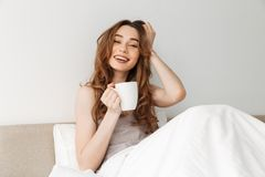 Portrait of fresh smiling woman resting after sleep in bed with Stock Photography