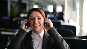 Portrait of friendly call center operator woman putting on headset in office. A smiling female hotline employee in