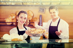 Portrait of friendly cheerful smiling couple at bakery display Royalty Free Stock Photo
