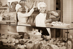 Portrait of friendly cheerful women at bakery display. With pastry royalty free stock photo