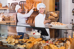 Portrait of friendly cheerful women at bakery display. With pastry stock photography