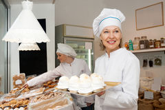 Portrait of friendly chef with pastry. Portrait of friendly chef at confectionery display with pastry royalty free stock images