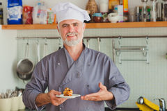 Portrait of Friendly chef present dessert Royalty Free Stock Image