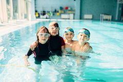 Friendly children with swimming goggles. Portrait of friendly children with swimming goggles in pool. Healthy and happy childhood concept. Funny children in Stock Photography