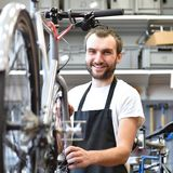 Portrait of a friendly and competent bicycle mechanic in a works. Hop repairs a bike Royalty Free Stock Photo