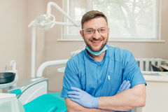 Portrait of friendly dentist in the dental office. With folded hands Stock Photos