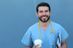 Portrait of friendly male doctor smiling holding a to go cup of coffee and a folder with documents Royalty Free Stock Images