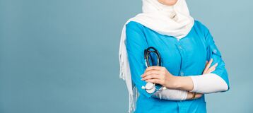 Portrait of a friendly, muslim doctor or nurse woman in hijab with a stethoscope on a blue background