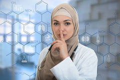 Portrait of friendly, muslim with hijab doctor showing shh sigh, silence. Stock Image