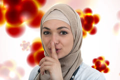 Portrait of friendly, muslim with hijab doctor showing shh sigh, silence. Stock Images