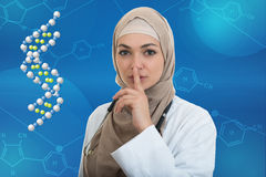 Portrait of friendly, muslim with hijab doctor showing shh sigh, silence. Royalty Free Stock Image