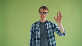 Portrait of friendly person guy waving hand looking at camera and smiling stock footage