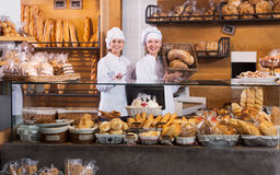 Portrait of friendly pleasant women at bakery display. With pastry royalty free stock photo
