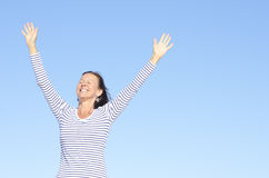 Portrait friendly relaxed positive woman. Beautiful happy looking mature woman in cheerful, positive, optimistic pose with arms up, isolated with blue sky as Royalty Free Stock Image