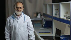 Portrait of friendly senior male doctor smiling stock video
