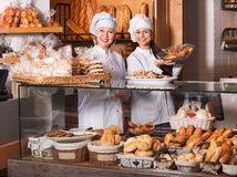 Portrait of friendly smiling women at bakery display. With pastry stock photos