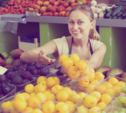 Portrait of friendly woman selling ripe fresh plums Royalty Free Stock Image