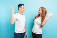 Portrait of friendly young men and women laughing and giving five, isolated on light blue background. Portrait of friendly young men and women in white t-shirts royalty free stock photo