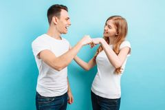 Portrait of friendly young men and women laughing and giving five, isolated on light blue background. Portrait of friendly young men and women in white t-shirts stock photography