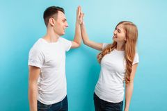 Portrait of friendly young men and women laughing and giving five, isolated on light blue background. Portrait of friendly young men and women in white t-shirts royalty free stock photography