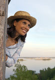 Portrait of friendly young woman in straw hat. Friendly young woman in straw hat against river at sunset Royalty Free Stock Image