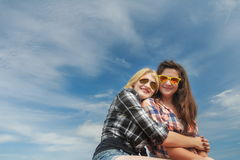 Portrait of friends embracing and posing to camera at cirrus blue sky Royalty Free Stock Photo