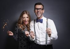 Couple celebrating New Year`s Eve. Portrait of friends with glowing sparklers in studio shot stock photo