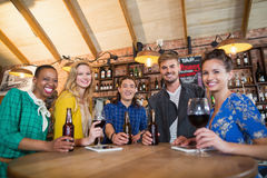Portrait of friends holding beer bottles and wine glasses on table. Portrait of cheering friends holding beer bottles and wine glasses on table in pub Royalty Free Stock Photos
