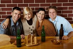 Portrait of friends in pub. Sitting at table, smiling at camera Royalty Free Stock Photos