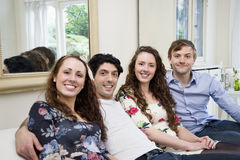 Portrait of friends sitting on sofa Royalty Free Stock Image