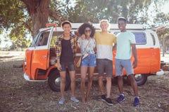 Portrait of friends standing against camper van at campsite Stock Images