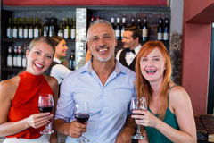 Portrait of friends standing at bar counter with a glass of red wine Royalty Free Stock Image