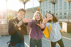 Portrait of friends teen boy and two girls smiling, making funny faces, showing victory sign in the street. City background,. Golden hour stock images