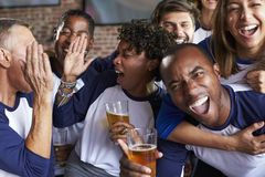 Portrait Of Friends Watching Game In Sports Bar On Screens Royalty Free Stock Images