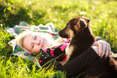 Portrait of friendship young girl with puppy. Closeup portrait of friendship young girl with puppy on green grass Stock Photography