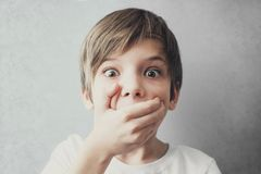 Portrait of frightened boy covering his mouth with his hand. Emotion concept Stock Photo