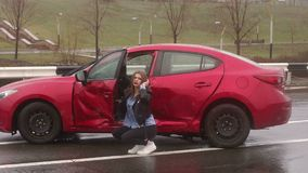 Portrait of a girl near her wrecked car after a severe accident on a wet road. Portrait of a frightened girl near her wrecked car after a severe accident on a stock footage