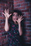 Portrait of a frightened young woman. Frightened young woman standing in corner of brick wall Royalty Free Stock Photo