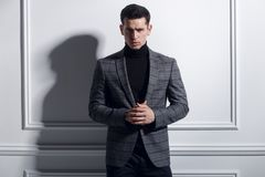 Portrait frontal d'une pose belle et élégante de jeune homme sûre dans le costume noir-gris élégant près du mur blanc, studio photos libres de droits