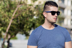 Portrait of frowning young strong man  on the street Stock Images